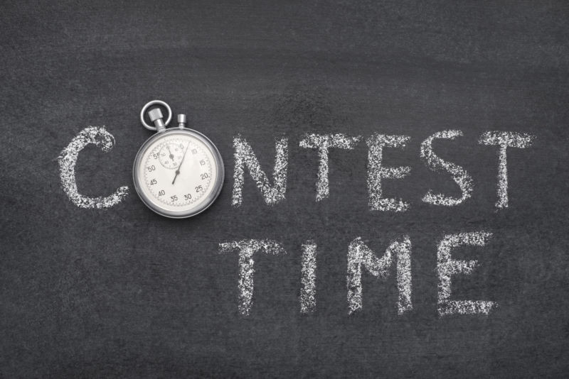 contest time phrase handwritten on chalkboard with vintage precise stopwatch used instead of O