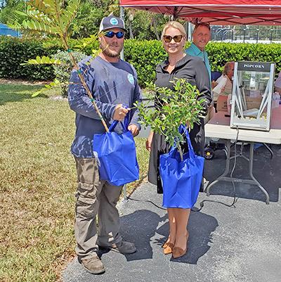 FKEC's Brandon Coile gives co-op member Sara Cizmas her Jamaican caper tree.