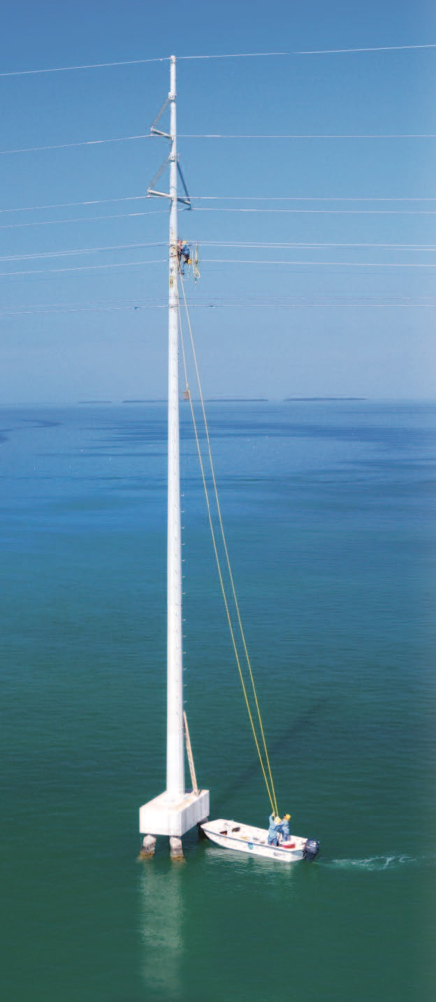 a worker climbs a power pole over the ocean. Two workers in a nearby boat hold onto lines attached to the pole.